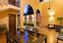 The rear patio with pool in this newly renovated colonial home in Santiago, Merida with outdoor lounging, colonial arches and availability all year round